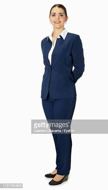 portrait of smiling businesswoman standing against white background - tenue soignée photos et images de collection