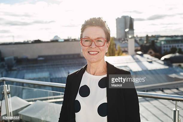 Portrait of smiling businesswoman standing in balcony against buildings