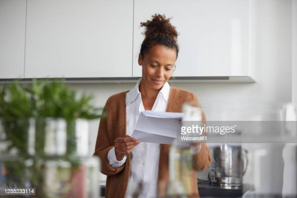 portrait of smiling businesswoman standing in kitchen looking at contract - mail stock pictures, royalty-free photos & images