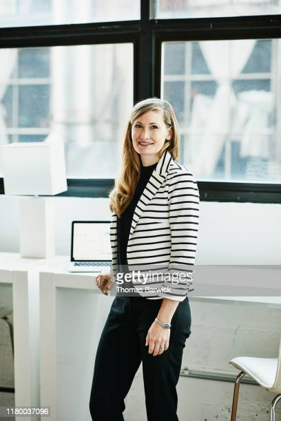 portrait of smiling businesswoman standing in office - striped blazer stock pictures, royalty-free photos & images