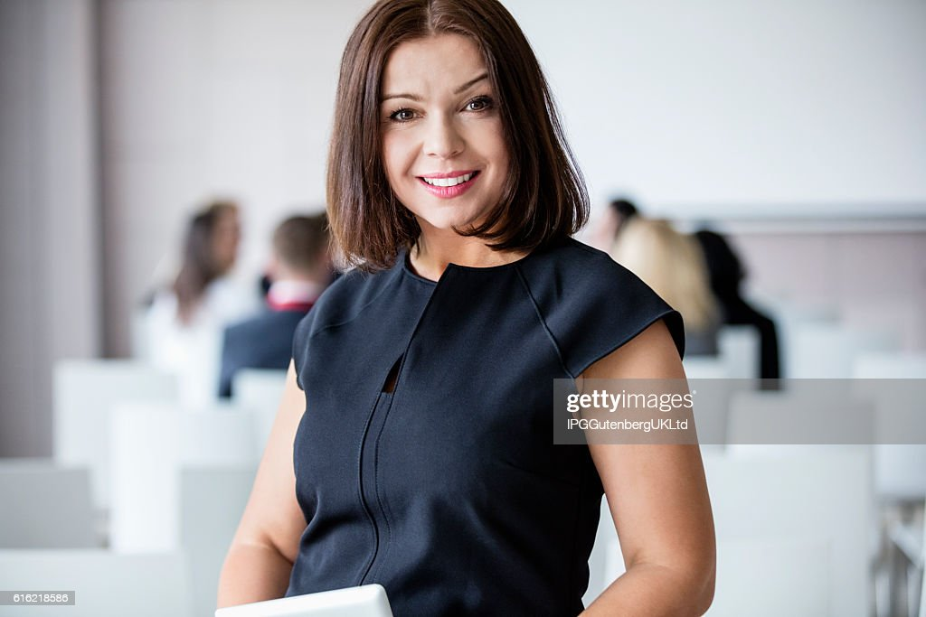 Portrait of smiling businesswoman standing in seminar hall : Stockfoto