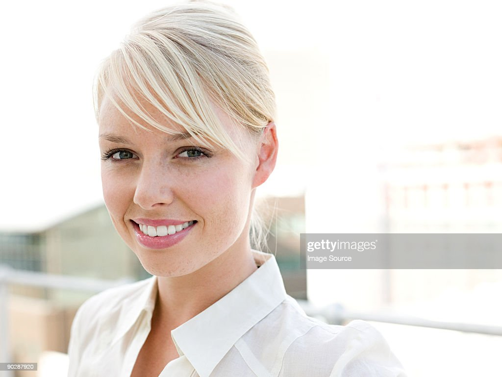 Portrait of smiling businesswoman standing on balcony : Stock Photo