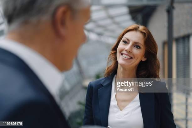 portrait of smiling businesswoman talking to businessman in office - chef stock-fotos und bilder