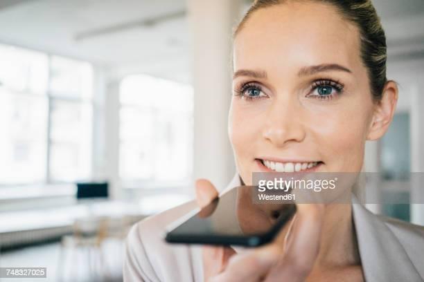 portrait of smiling businesswoman using cell phone - voce foto e immagini stock