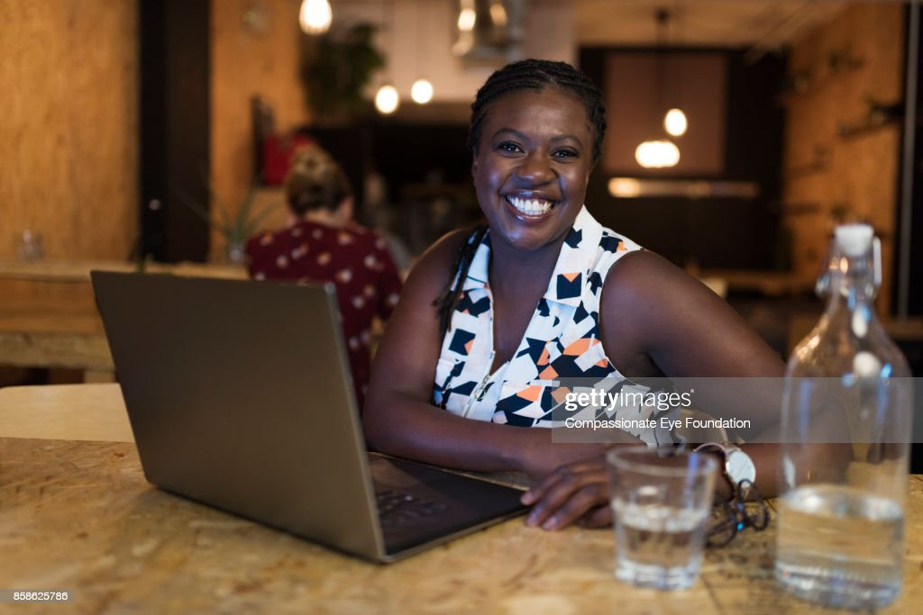 Portrait of smiling businesswoman using laptop in cafe : Stock-Foto