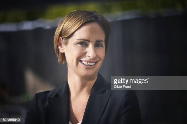 portrait of smiling businesswoman wearing braces - black blazer stock pictures, royalty-free photos & images