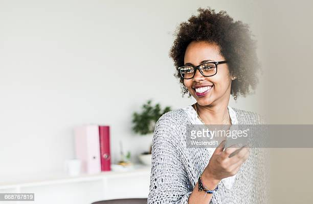 Portrait of smiling businesswoman wearing glasses in office