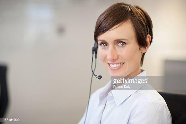 Retrato de la sonriente empresaria usando auriculares