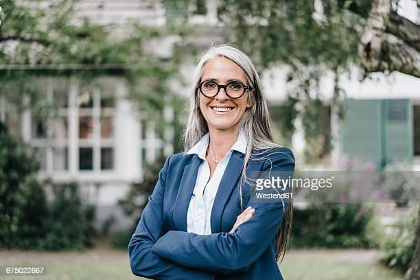 portrait of smiling businesswoman wearing spectacles standing in the garden - solo una donna matura foto e immagini stock