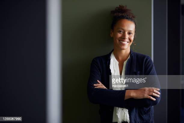 portrait of smiling businesswoman with arms crossed in office - black blazer stock pictures, royalty-free photos & images