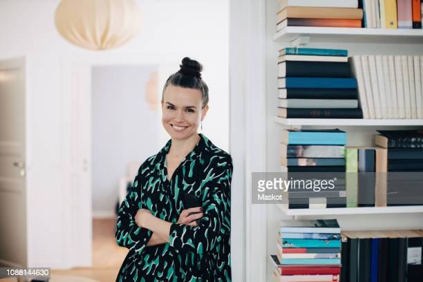 portrait of smiling businesswoman with arms crossed leaning on wall at home - rodete fotografías e imágenes de stock