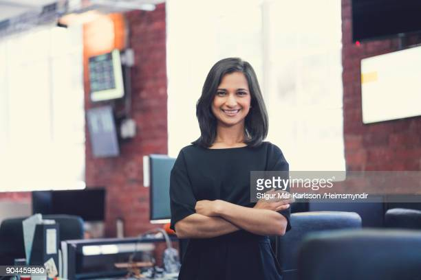 portrait of smiling businesswoman with arms crossed - indian ethnicity stock pictures, royalty-free photos & images