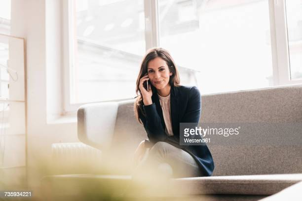 Portrait of smiling businesswoman with cell phone on couch