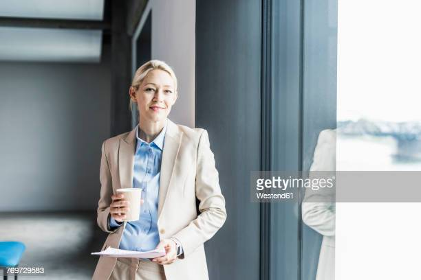 Portrait of smiling businesswoman with coffee and documents at the window