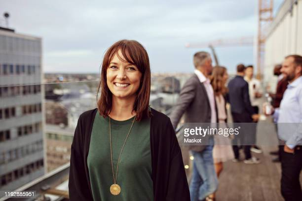 portrait of smiling businesswoman with colleagues in background standing on terrace during party - femmes d'âge moyen photos et images de collection