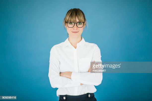 portrait of smiling businesswoman with glasses - arme verschränkt stock-fotos und bilder