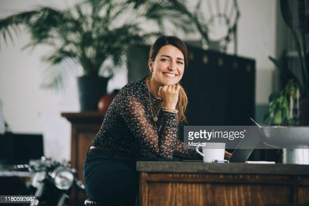 portrait of smiling businesswoman with hand on chin sitting at kitchen island in creative office - agence de design photos et images de collection
