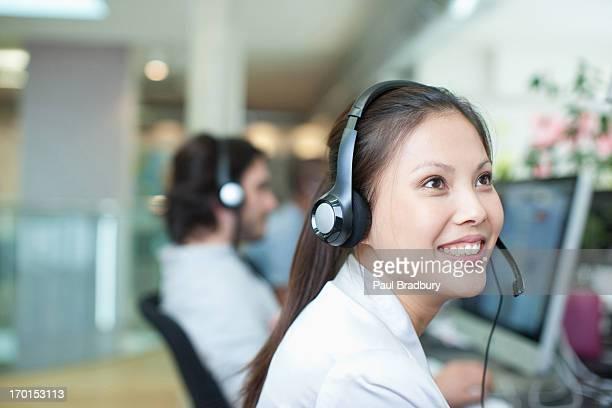 笑顔のビジネスウーマンのポートレート、ヘッドセットで、オフィスでコンピューター