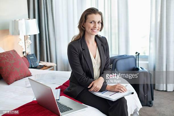 Porträt von lächelnd Geschäftsfrau mit Papierkram mit laptop in h