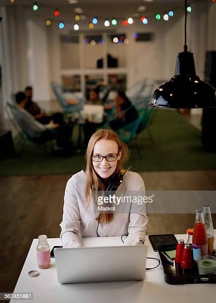 Portrait of smiling businesswoman working late on laptop in creative office