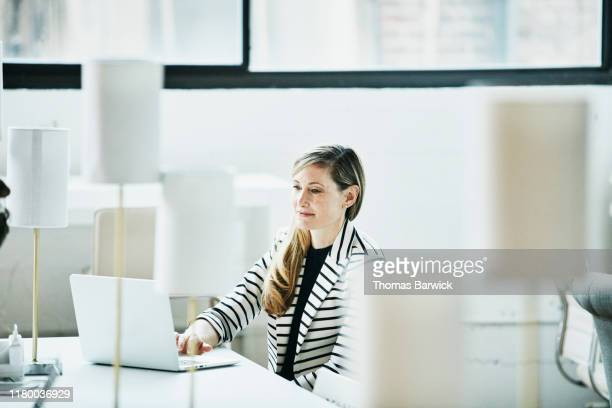portrait of smiling businesswoman working on laptop in coworking office - striped blazer stock pictures, royalty-free photos & images