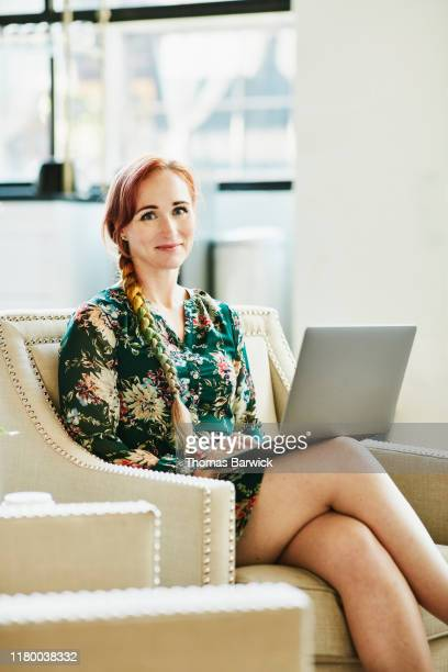 portrait of smiling businesswoman working on laptop in coworking office - green dress stock pictures, royalty-free photos & images