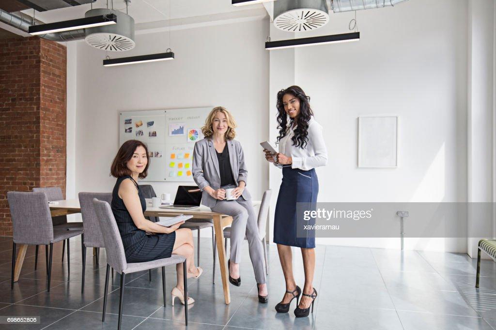 Retrato de sorrindo empresárias na sala de diretoria : Foto de stock