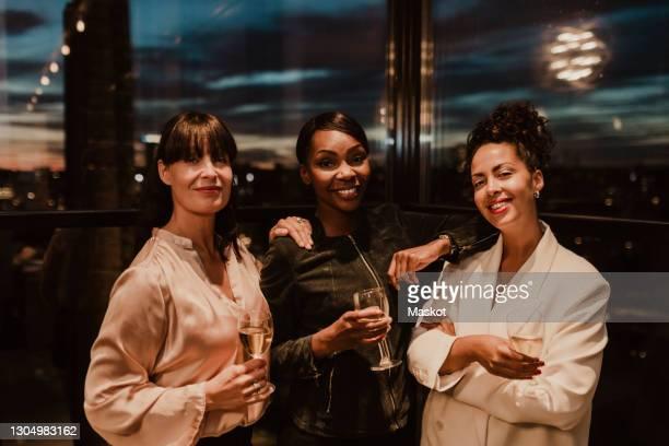 portrait of smiling businesswomen with wineglasses during office party - launch event bildbanksfoton och bilder