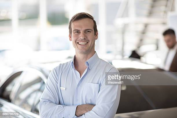 Portrait of smiling car dealer in showroom