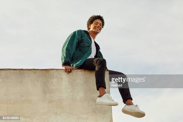 portrait of smiling carefree man at rooftop - sitting stock pictures, royalty-free photos & images