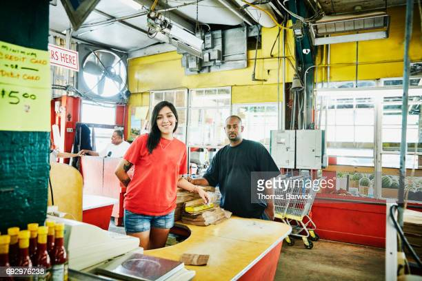 Portrait of smiling cashier and bagger working at produce market