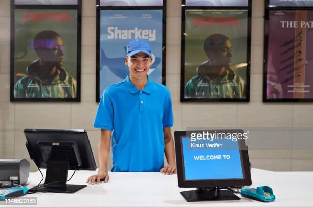 portrait of smiling cashier at theater - ポロ ストックフォトと画像