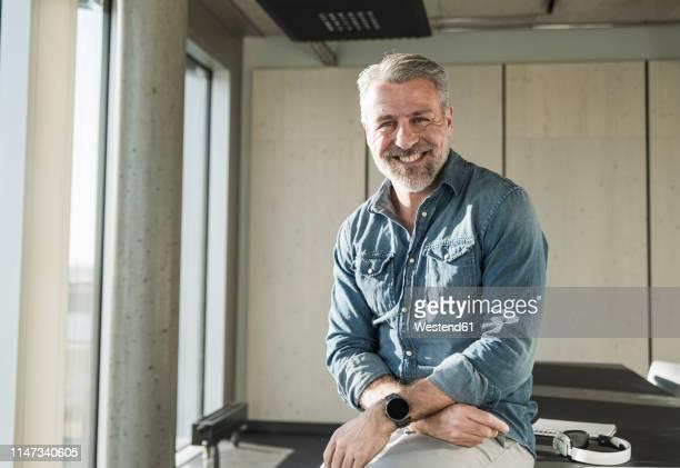 portrait of smiling casual mature businessman in office - solo un uomo maturo foto e immagini stock