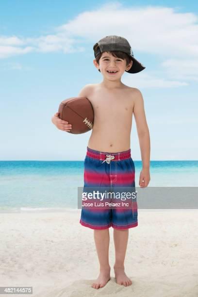 portrait of smiling caucasian boy with football on beach - knaben in badehosen stock-fotos und bilder