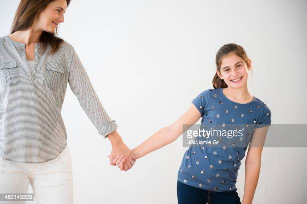 Portrait of smiling Caucasian daughter holding hands with mother