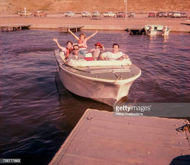 Portrait of smiling Caucasian family waving on boat near dock