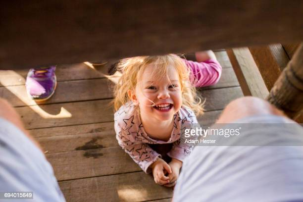 Portrait of smiling Caucasian girl laying underneath table