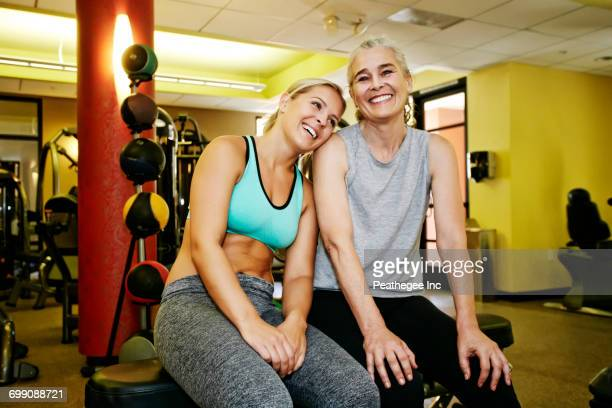 Portrait of smiling Caucasian mother and daughter in gymnasium