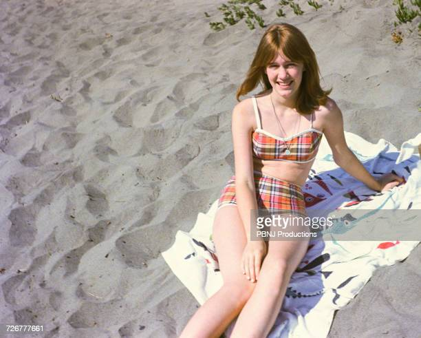 portrait of smiling caucasian teenage girl sitting on blanket at beach - swimwear photos stock photos and pictures