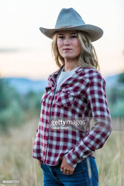 Portrait of smiling Caucasian teenage girl wearing cowboy hat at sunset