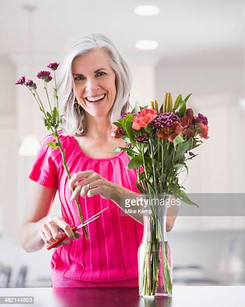 Portrait of smiling Caucasian woman arranging flowers