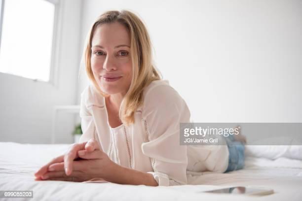 portrait of smiling caucasian woman laying on bed - jersey city - fotografias e filmes do acervo