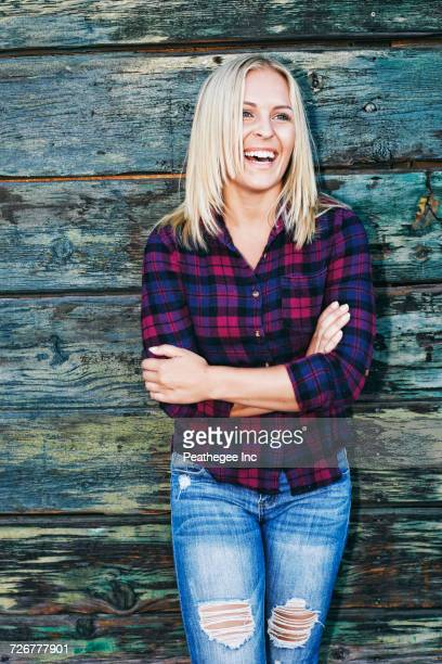portrait of smiling caucasian woman leaning on wooden wall - plaid shirt stock pictures, royalty-free photos & images