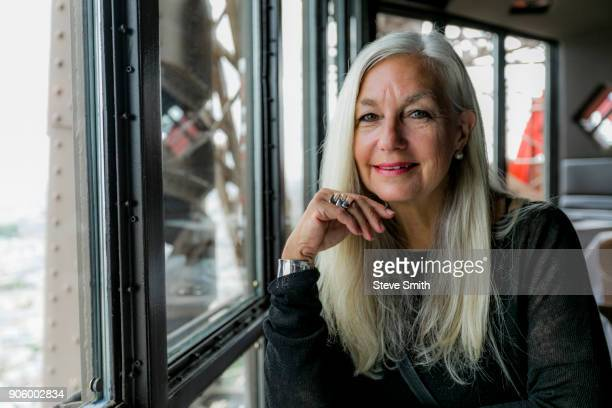 portrait of smiling caucasian woman near window - sayings stock pictures, royalty-free photos & images