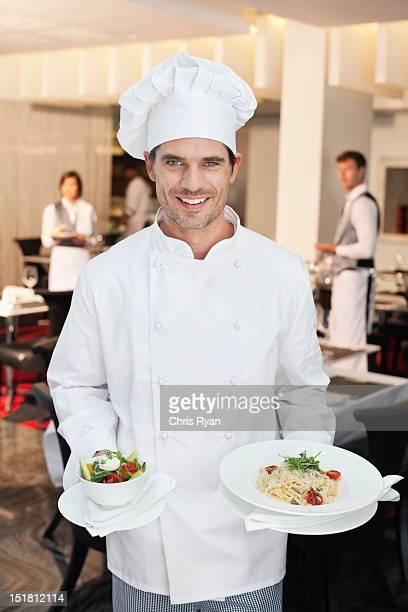 Porträt von lächelnd Chefkoch mit Salat oder Vorspeise
