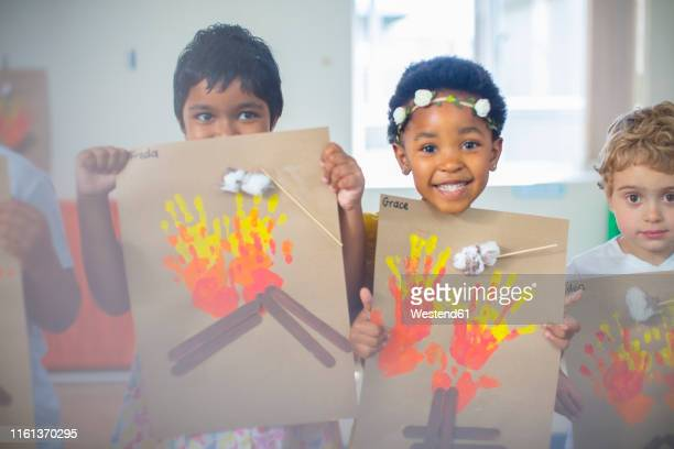 portrait of smiling children presenting images of fire in kindergarten - 4 girls finger painting stock photos and pictures