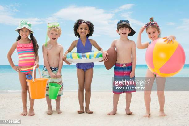 Portrait of smiling children with toys on beach