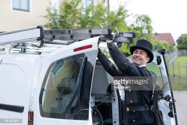 portrait of smiling chimney sweep at his van - schornsteinfeger stock-fotos und bilder