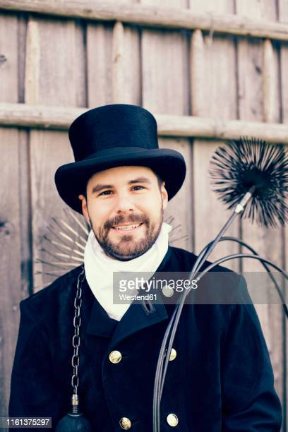 portrait of smiling chimney sweep - schornsteinfeger stock-fotos und bilder