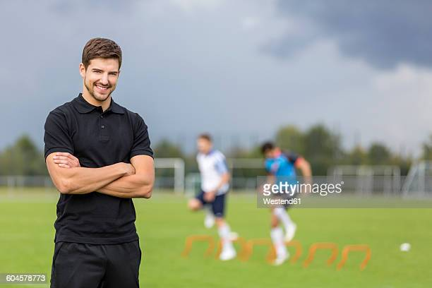Portrait of smiling coach with soccer players in background